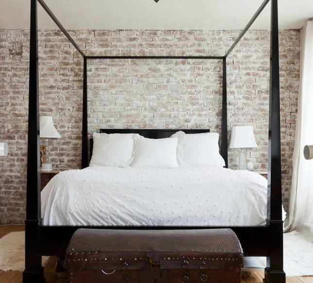 Nice master bedroom with a dark wood canopy bed with a trunk at its foot with a