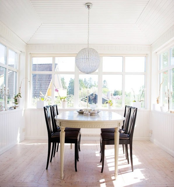 Bright white sunroom with an oval Gustavian white table, dark wood dining chairs, and a crystal ball chandelier