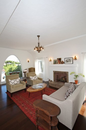 Alternative view of the living room with arched window, club chairs and a grey sofa with cococozy pillows and throws, dark wood floors, a red Moroccan rug, a brick fireplace and a chandelier
