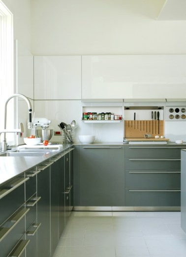 Kitchen with dark grey cabinets with long silver drawer pulls, white tile floors and white upper cabinets with no visible drawer pulls