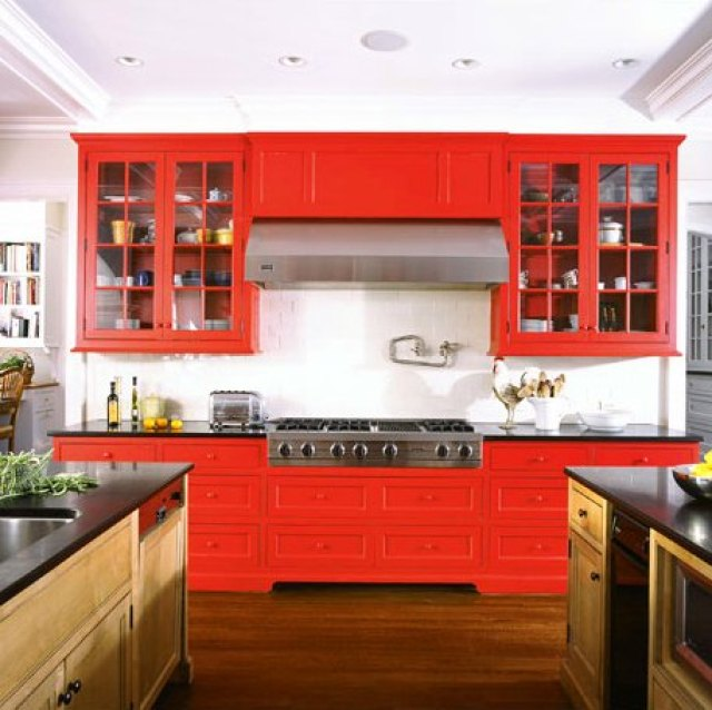 Kitchen with black counter tops, bright red drawers and cabinets and stainless appliances
