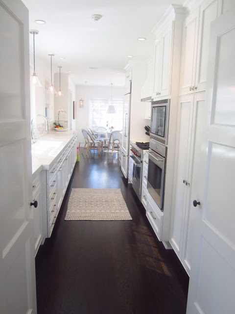 Galley kitchen with white counters and cabinets and dark wood floors