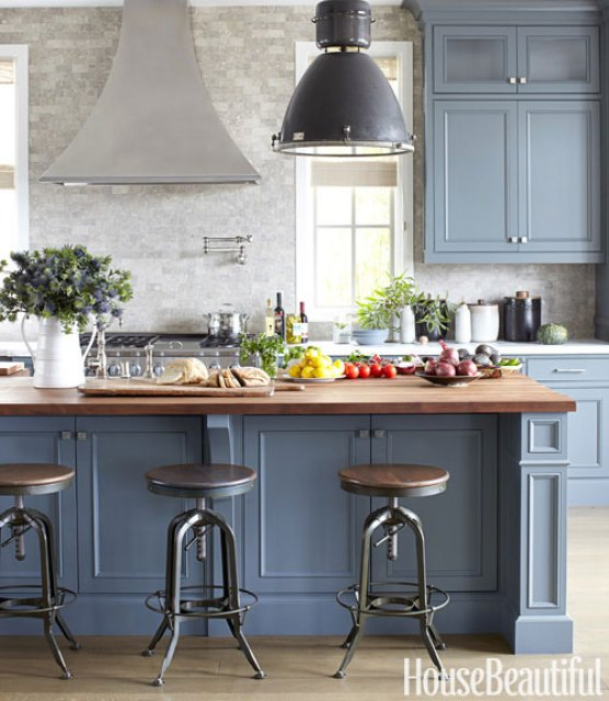 kitchen with black pendant lights, blue grey cabinets, turn stools, butcher island and tumbled marble backsplash