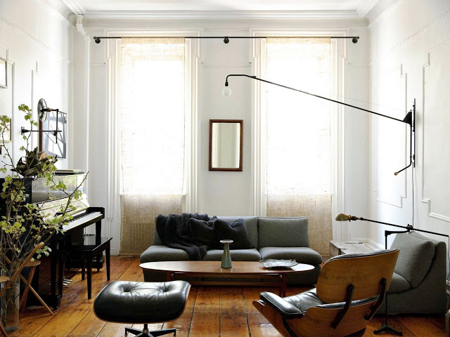 living room with white walls etched rectangle wall modling, wood floors, a piano, gray sofas and a black leather ottoman chair