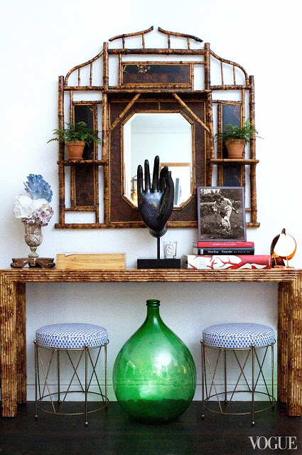 Side table in Rebecca de Ravenel's dining room with two metal stools with blue and white seats, a large glass bottle and faux bamboo mirror