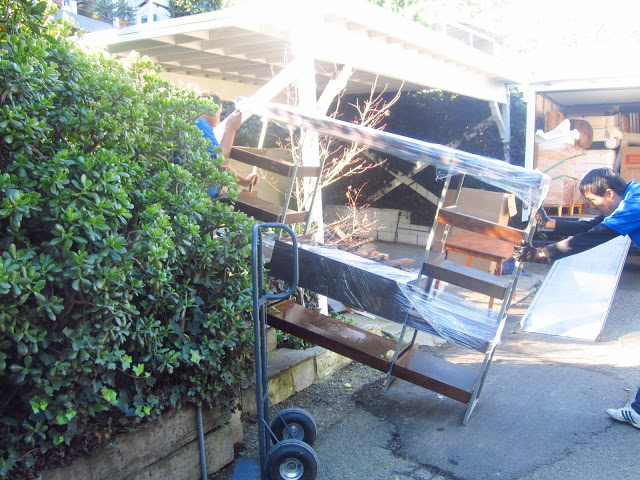 two men moving a large tv mount and bookcase wrapped in plastic up a flight of flagstone stairs