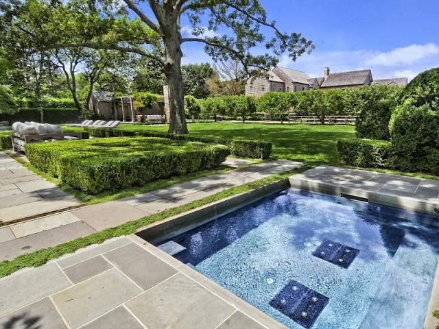 Backyard of an East Hampton compound with a pool, walkway and well kept hedges