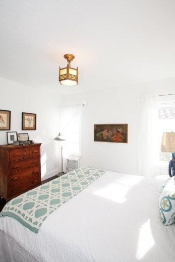 Alternative view of the bedroom with a view of a redwood chest of drawers, small paintings and a small Moroccan inspired pendant light