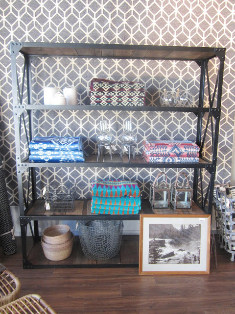 A metal shelf holding small objects propped in front of a graphic patterned flat weave dhurrie wool rugs are displayed hanging on the store's walls like wallpaper