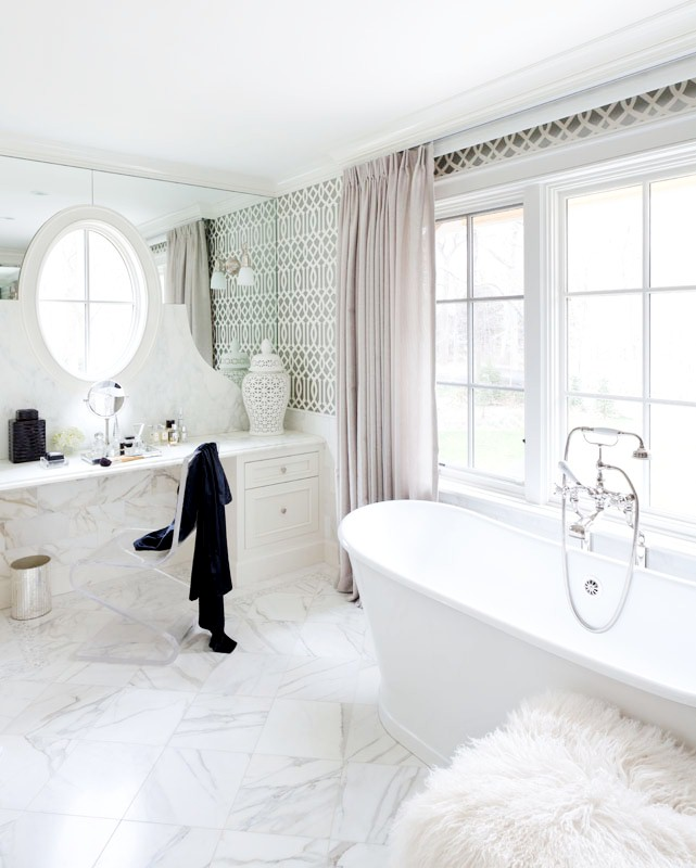 Girly bathroom with white marble floor, stand alone bathtub, Trellis wallpaper, vanity with a lucite chair under an oval window