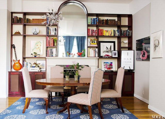 Dining room with Madeline Weinrib rug, a large oval table, plaid upholstered chairs, a pass through window to the kitchen with wooden bookcases holding books, art and other small items