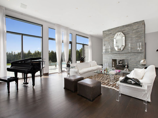 living room in the Hamptons with a grand piano, wood floor, floor length glass windows and door, white couches and lucite coffee table and accent tables and a stone fireplace