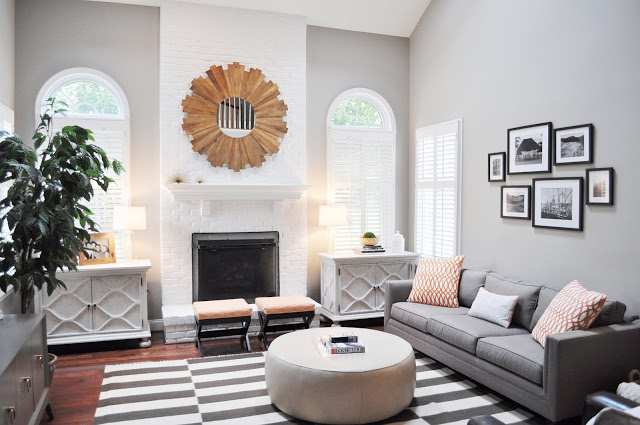 family room with grey walls, a grey and white striped rug, a white painted brick fireplace and a round ottoman