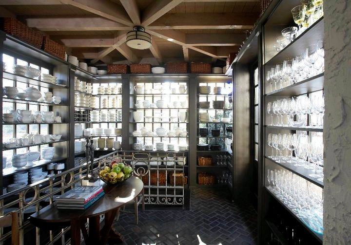 Butler's pantry with herringbone brick floor, exposed beams and open shelving light from behind