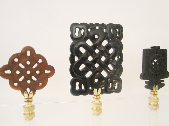 Close up of three stone finials, two black on brown