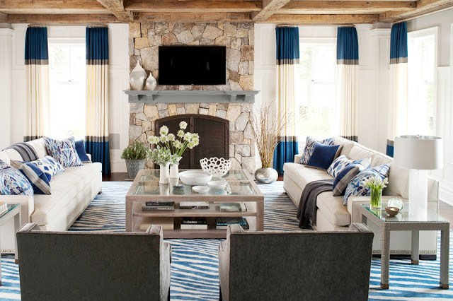Living room with color block curtains, a stone fireplace, dueling facing sofas, exposed beam ceilings, and a large coffee table