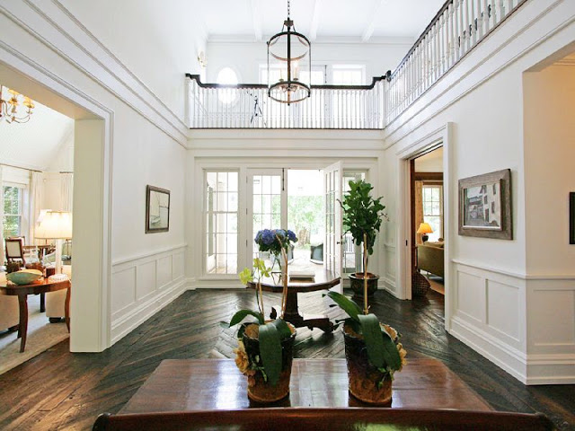 foyer with herringbone wood floors, french doors, double height entry and a large pendant light