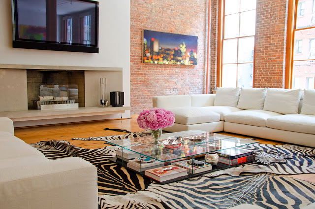 Alternative view of living room with the Cassina coffee table above. Here you can see the white sectional sofa, zebra print rugs, brick walls, fireplace, wall mounted TV and large windows.