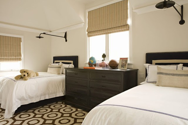 Twin bedroom with simple brown headboards with off white time, a brown and white graphic print rug, a dark wood chest of drawers, black wall mounted lights and roman shades on the window