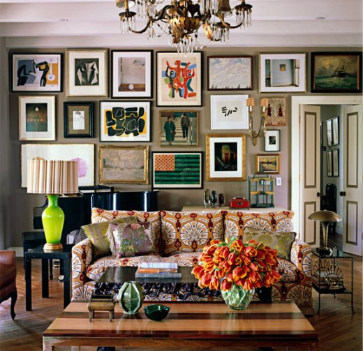 Living room with on wall covered in art, herringbone wood floor, a brass chandelier, a wood coffee table and a bright patterned couch