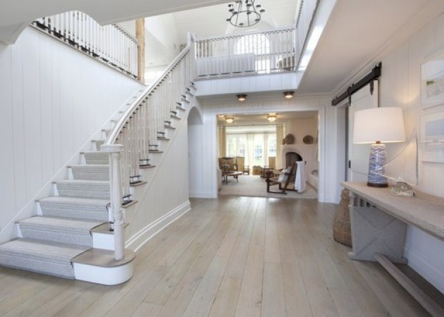 foyer with white wood staircase and oak wood floors