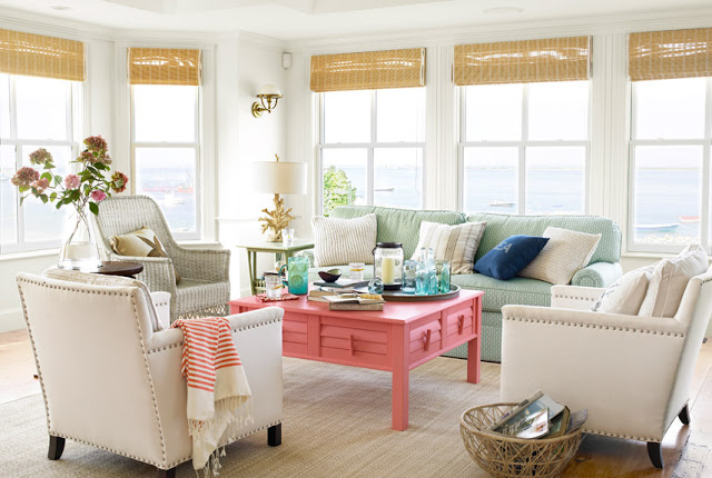 costal living room with many windows, a pink coffee table, three upholstered  cream colored armchairs and a mint green sofa