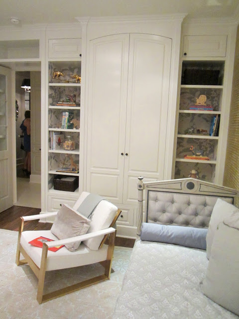 "Built in bookshelves and cabinets in the baby room in the Windsor house, the bookshelves are lined with Schumacher's ""Jungle Play"" wall covering"