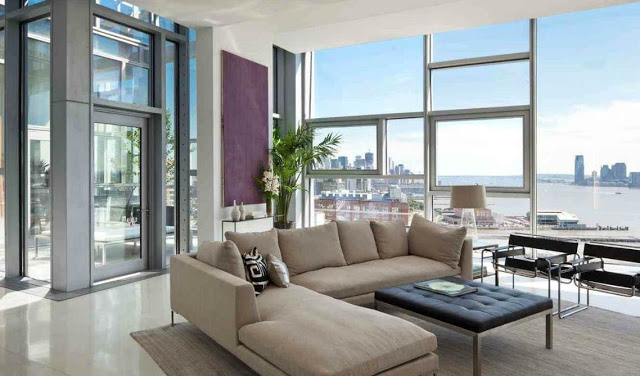 living room with encasement window walls with an amazing view of NYC, gray sectional sofa, black ottoman and modern black chairs