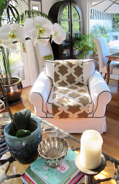 Throw on a white arm chair with black piping, a glass coffee table with metal detailing, books and fresh flowers and plants