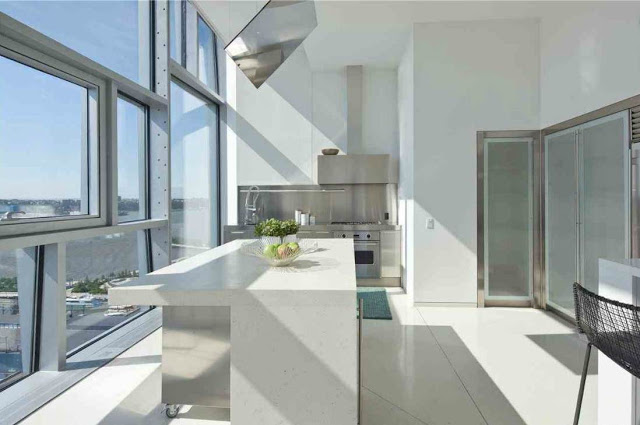 Sleek, modern kitchen with stainless appliances and cabinets. The island has a stainless base with a white counter top