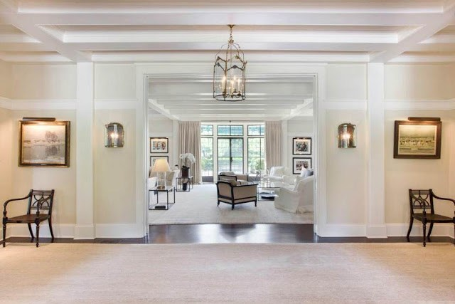 foyer in a manison with rug, pendant light and a view into the main living room