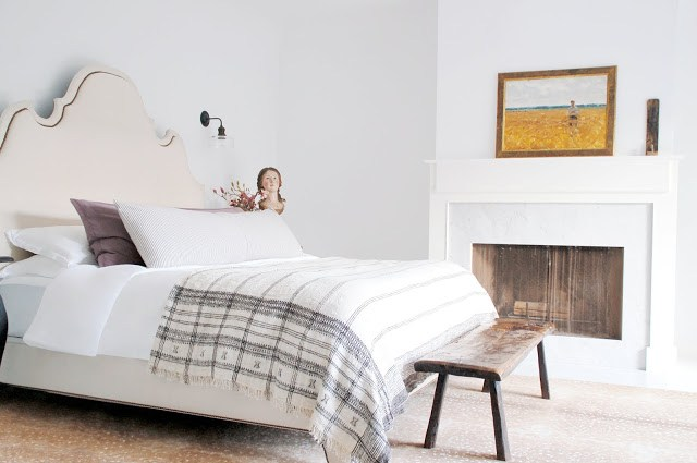 bedroom with upholstered headboard, fireplace and reclaimed wood bench at the foot of the bed