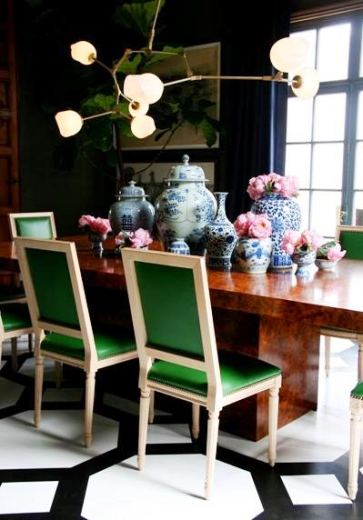 Dark dining room with black and white painted floor, brown stone table surrounded by upholstered green chairs, on the table are blue and white chinese pots in different sizes and shapes and above it all if a modern chandelier