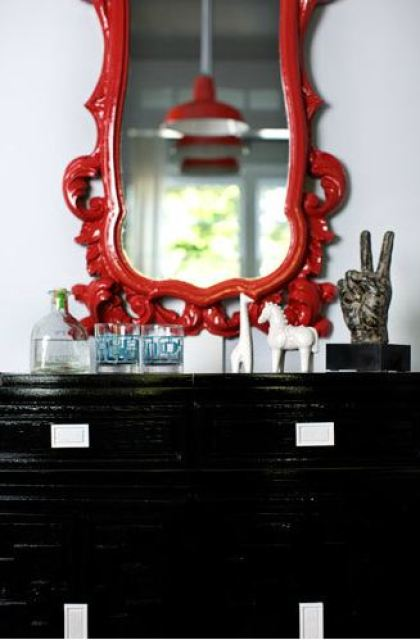 Glossy black chest of drawers with a red traditional mirror