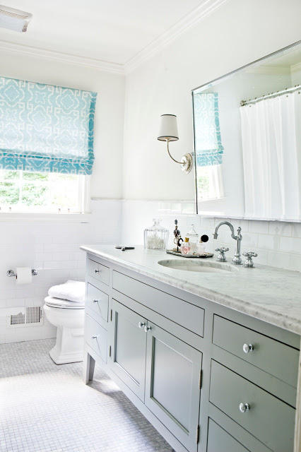White bathroom with light blue Roman shades, marble counters, hexagon mosaic tile floor and a large mirror