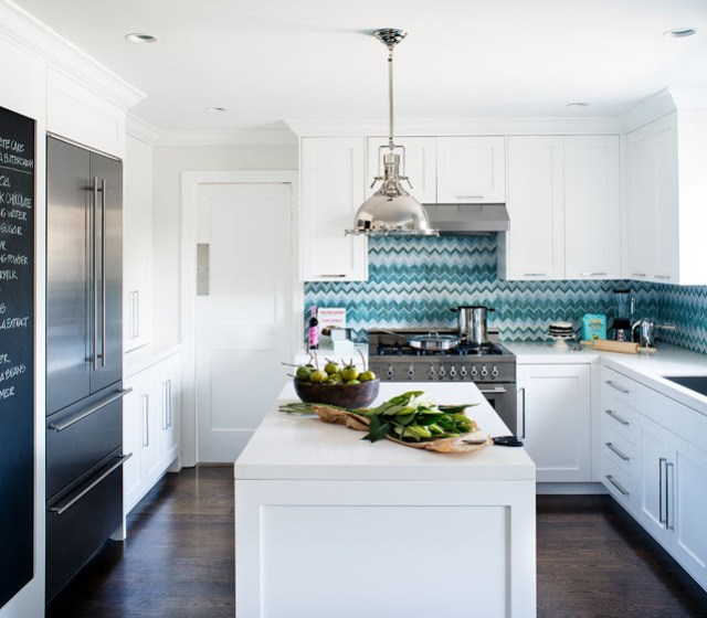 kitchen with blue and white zig zag chevron tiles, white cabinets and center island, polished metal stove, french door refrigerators and a chalkboard wall by Jute