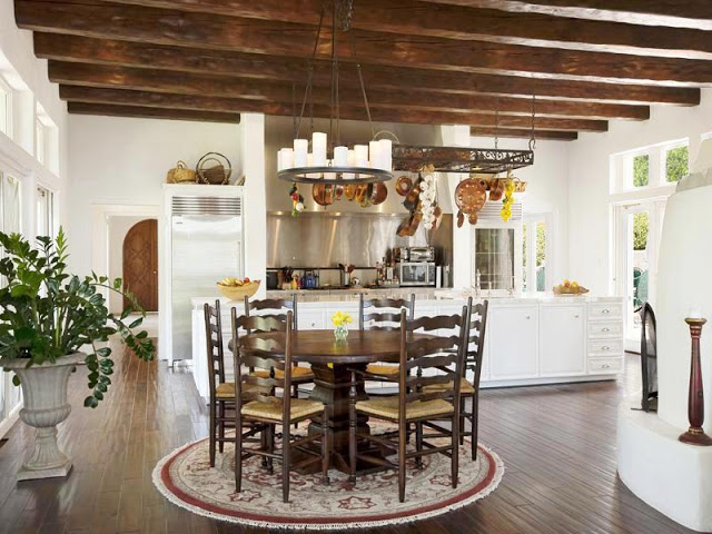 Open kitchen with round wood breakfast table surrounded by high back wood chairs on a round rug, wood floors, exposed beams and a metal chandelier