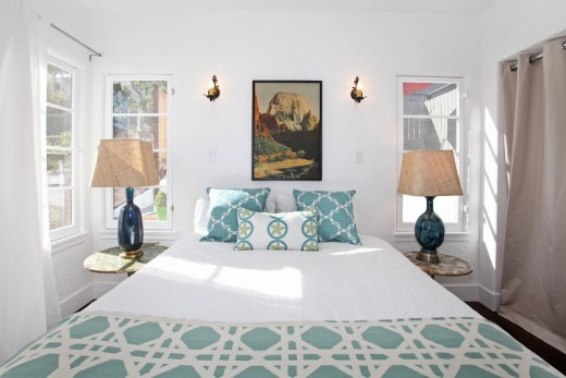 White bedroom in a Spanish Style home with vintage lamps on matching side tables, a picture of a mountain above the bed with COCOCOZY pillows and throw in light blue