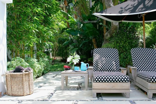 Outdoor patio with polka dot chaise lounge cushions on teak lounge chairs