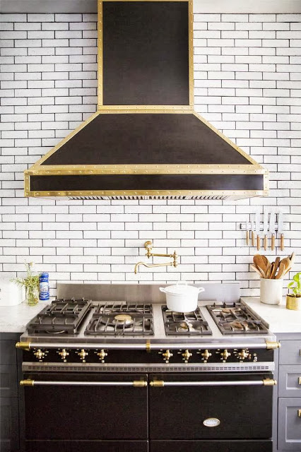 Kitchen in a New York City apartment with subway tile backsplash and a hood with brass accents