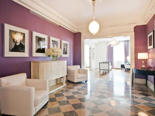 Foyer in a purple park avenue apartment with a checkered marble floor, coffered ceiling, pendant light, white armchairs and a white chest of drawers