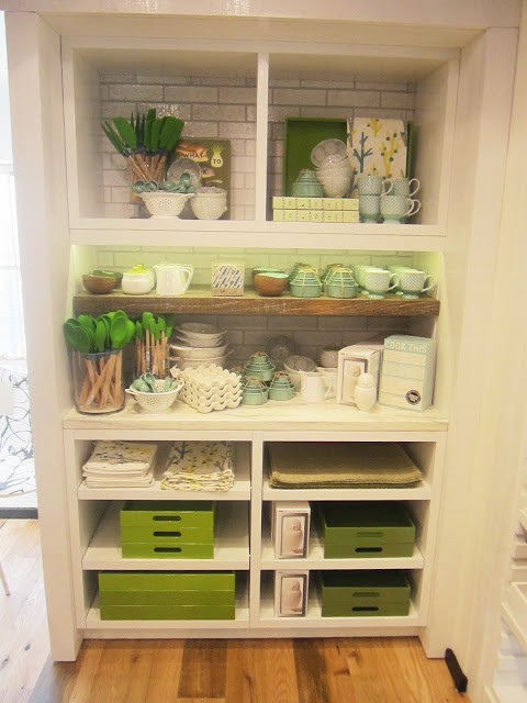 White cabinet holding kitchen accessories in a variety of shades of green