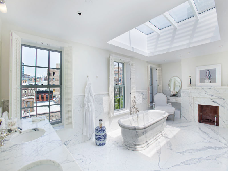 Cool master bathroom with a marble bathtub and fireplace encasement windows with views of the Highline