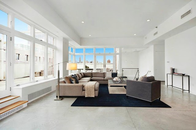 Modern living room in a NYC Penthouse with a tan sectional sofa and navy rug
