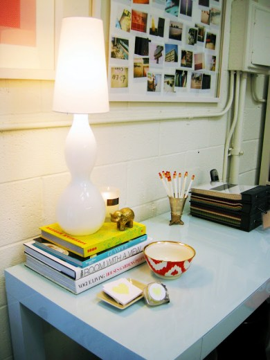 Close up of the lamp, books, card holder and ikat bowl on the light blue glossy Parsons Desk in the office