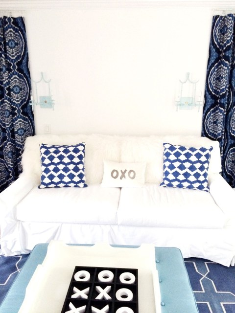 Blue and white living room in an East Hampton home with ikat print curtains