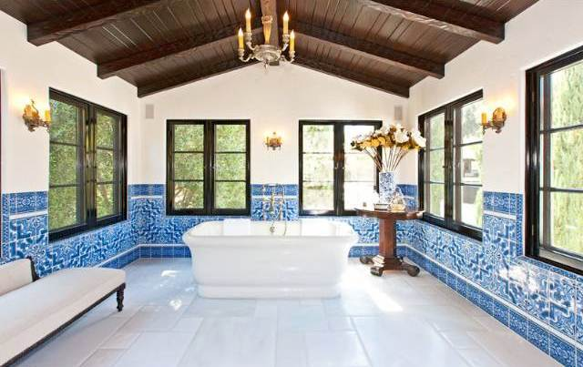 Blue and white tiled bathroom with wooden ceiling with visible beams, a chandelier and stand alone bath tub