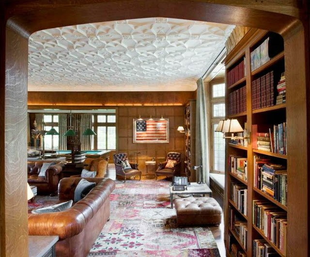 mansion with wood paneled library, built in bookshelves, brown leather sofas and chairs and a decorative ceiling