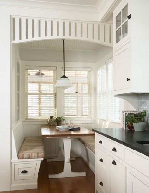 rehkamp larson architects' breakfast nook with booth banquette style bench seating, a wooden table with white legs, pendant light and built in wood slat ceiling