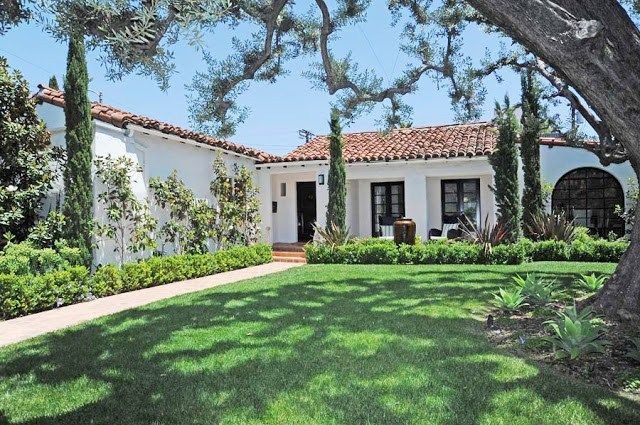 exterior of a white Spanish style home with red tile roof, a brick walkway, grass and a large tree